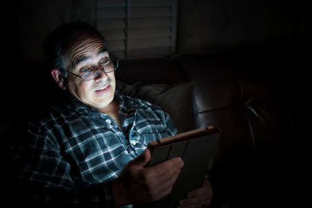 fifties: Middle aged man wearing pajamas reading tablet at night in bed looking scared or surprised with copy space