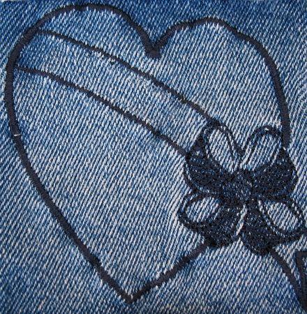 Un denim corazón cosido en blanco con una bandera y un arco.
