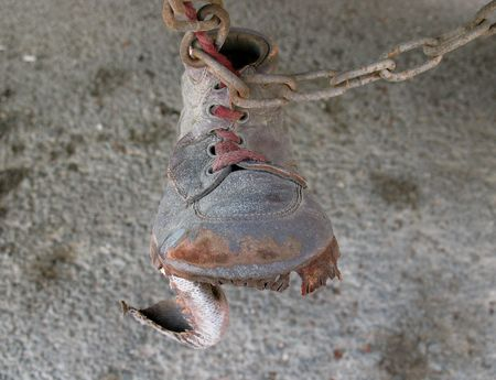 superstition: An old, torn shoe hanging from a rusty metallic chain underneath a bus (a superstition in Lebanon to ward off the evil eye from cars, buses, six-wheelers, �!) Stock Photo