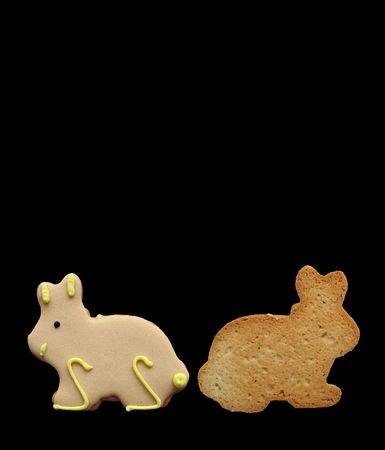 Dos en forma de conejito de Pascua galletas aislados sobre un fondo negro.