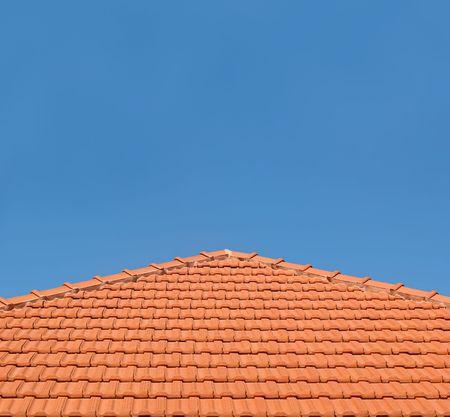 Un tejado de azulejos de color naranja-contra un claro cielo azul.