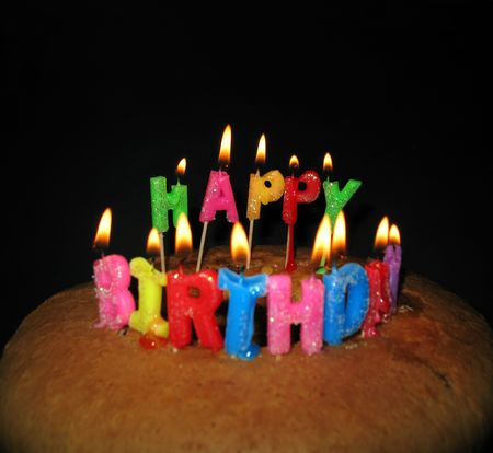 lighted: Lighted candles on a birthday cake on black background. The focus is on the word HAPPY. Stock Photo