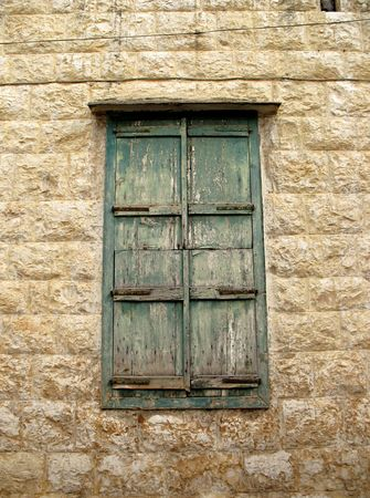 bolted: A bolted green window, its very old with the painting peeling off of it. Lebanon.