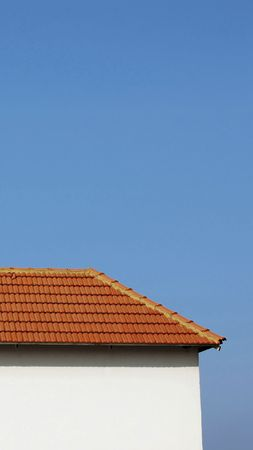 The half part of a tiled rooftop and white side of a house against a blue sky. photo