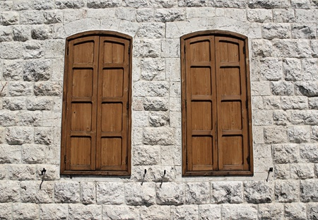 A limestone wall with two closed windows. Stock Photo - 8241028