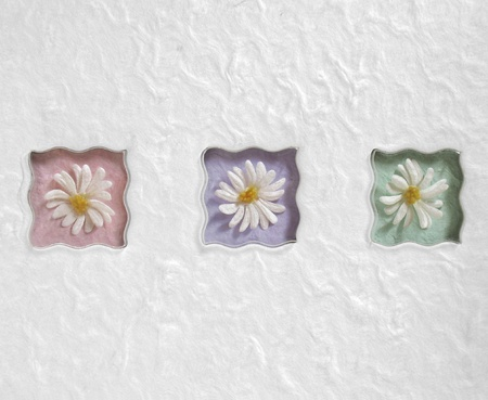 Three wavy artificial daisy flowers on a white background. photo