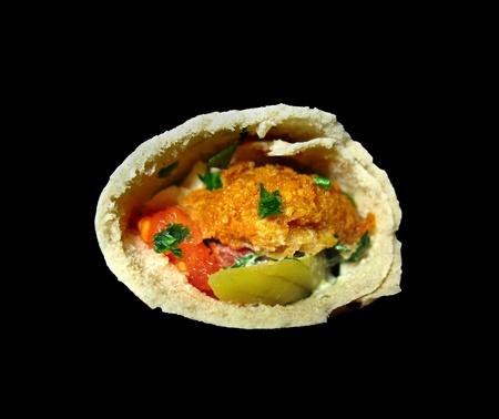 Delicious close-up of a traditional Lebanese snack, falafel sandwich, isolated on black. photo