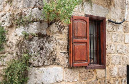 Una ventana rústico con persiana de madera en el exterior de una casa libanesa