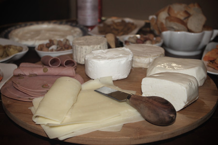 Various slices of cheese and ham on a round wooden plate  photo