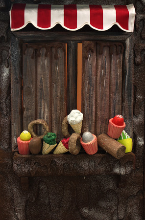 Various fake cupcakes, candy, doughnuts, and ice cream cones decoration on wooden window ledge  photo