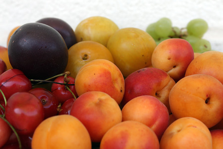 A mix of fresh summer fruits on white  photo