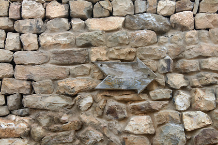 A wooden arrow pointing on a old stone wall  photo
