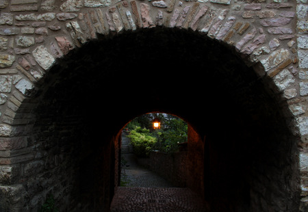 lighted: An Arch in Assisi with a lighted lamp.