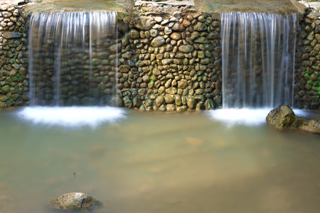 Two small waterfalls separated by a stone wall. photo