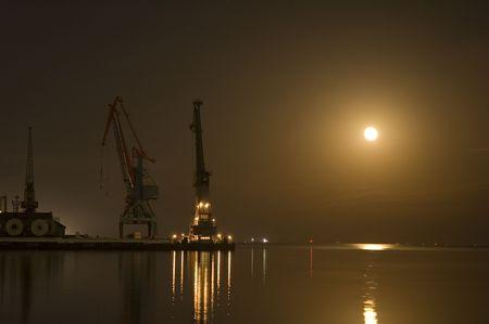 baku: Cranes at Baku port at night with moon Stock Photo