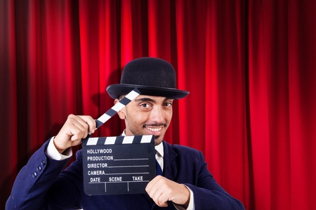 Man with movie clapper on curtain background photo