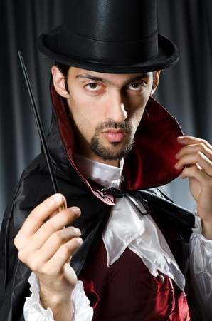 conjuror: Magician in the dark room with wand Stock Photo