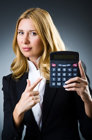 Businesswoman with calculator in business concept photo