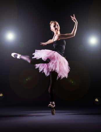 Ballerina tanzt im dunklen Studio