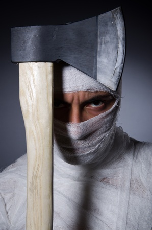 mummified: Mummy with axe in halloween concept