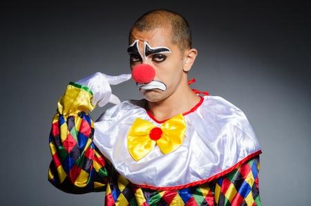 Sad clown against dark background photo
