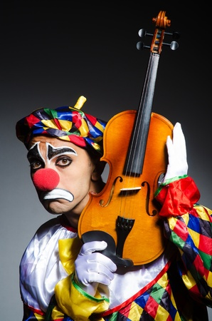 Sad clown performing at vioin photo