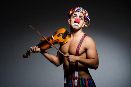 Sad clown performing at vioin photo