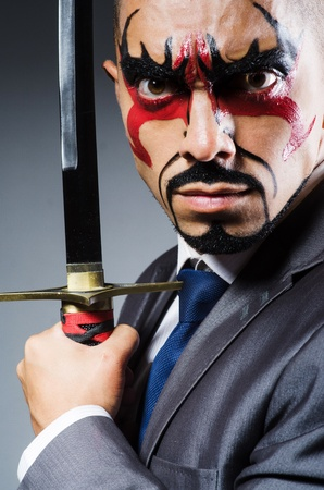 aggressive people: Man with face paint and sword