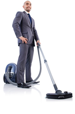 Businessman doing vacuum cleaning on white photo