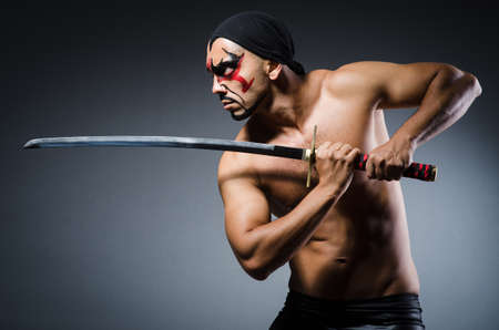 ninja ancient: Man with sword and face paint Stock Photo