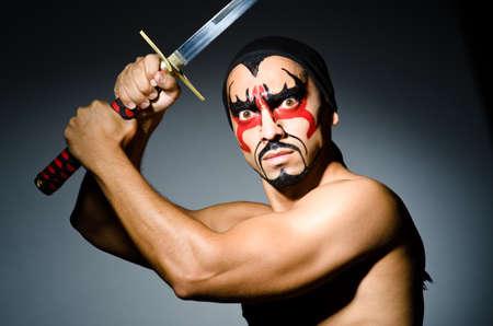 samurai warrior: Man with sword and face paint Stock Photo