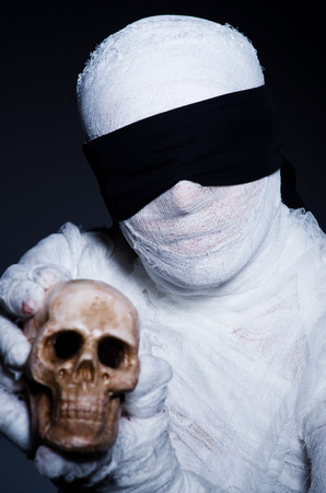 Mummy with skull in dark room photo