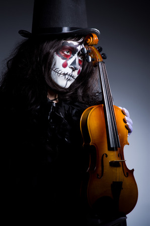 Monster playing violin in dark room photo