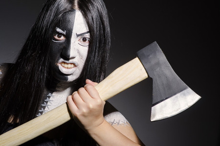 Woman monster with axe in dark room photo