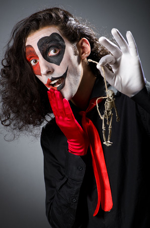 harlequin clown in disguise: Funny man with skeleton in hands Stock Photo