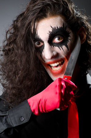 harlequin clown in disguise: Funny joker with sharp knife