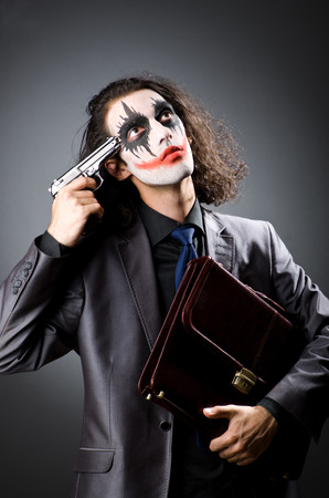 harlequin clown in disguise: Joker with gun and briefcase Stock Photo