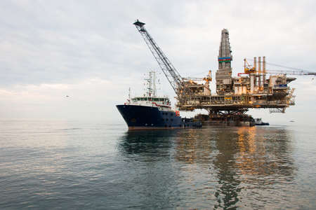 Oil rig being tugged in the sea photo