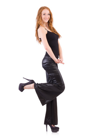 Redhead woman in black bell bottom pants on white photo