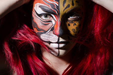 Woman with face painting in dark room photo