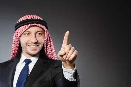 Arab businessman pressing virtual buttons against grey background photo