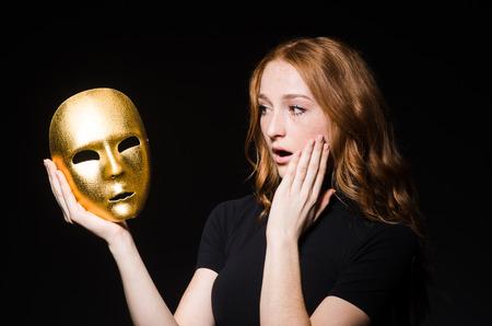 hipocresía: Redhead mujer m�scara iwith en consept hipocres�a contra el fondo negro Foto de archivo
