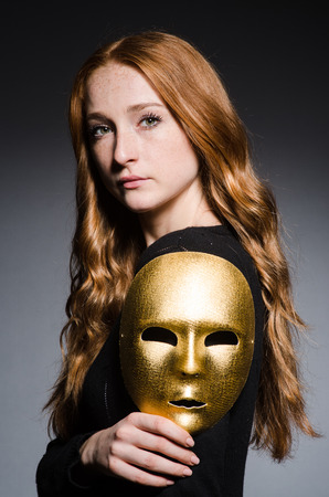 hypocrisy: Redhead woman iwith mask in hypocrisy consept against grey background