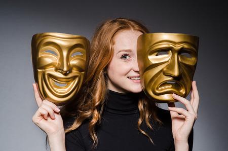 Redhead Frau iwith Masken in Heuchelei consept gegen grauen Hintergrund