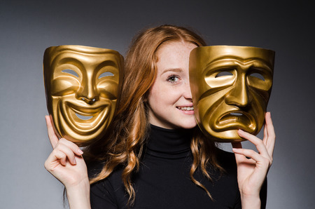hypocrisy: Redhead woman iwith masks in hypocrisy consept against grey background