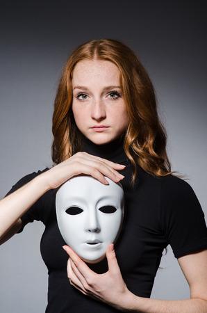 hipocres�a: Redhead mujer m�scara iwith en consept hipocres�a contra el fondo negro Foto de archivo