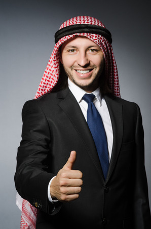 qameez: Arab businessman with thumbs up againt grey background