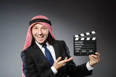 Arab man with movie clapper against grey background photo