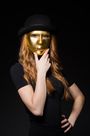 hypocrisy: Redhead woman iwith mask in hypocrisy consept against black  background