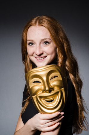 insincere: Redhead woman iwith mask in hypocrisy consept against grey background